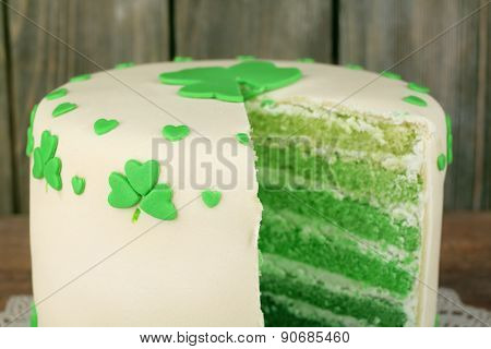 Sliced cake for Saint Patrick's Day on wooden planks background