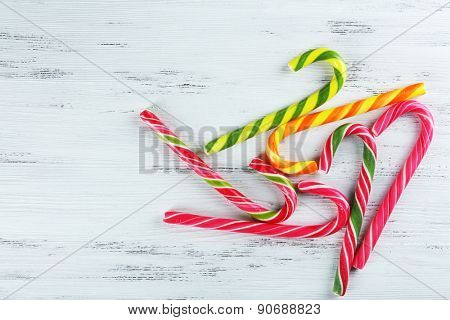 Colorful candy canes on wooden background