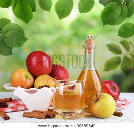 Apple cider in bottle with cinnamon sticks and fresh apples on nature background