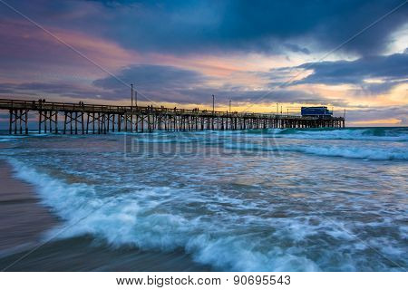 Waves In The Pacific Ocean And The Newport Pier At Sunset, In Newport Beach, California