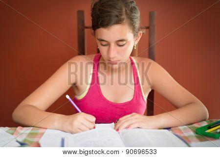 Hispanic teenage girl studying at home