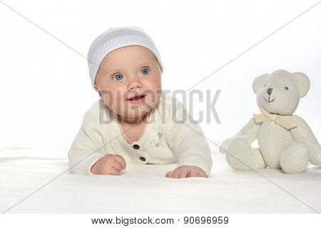 baby girl child lying down on white blanket smiling happy white clothing fashion portrait face studio shot isolated on white caucasian teddy bear