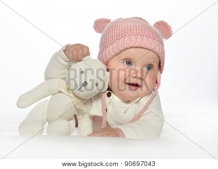 baby girl child lying down on white blanket smiling happy pink fashion portrait face studio shot isolated on white caucasian hat teddy bear