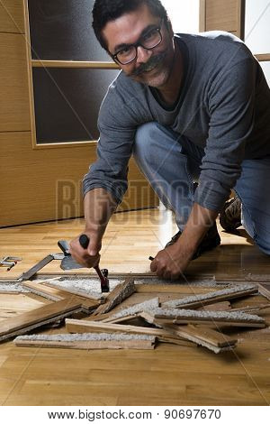 Vertical image of a worker disassembling wooden floor ruined from moisture and water leak
