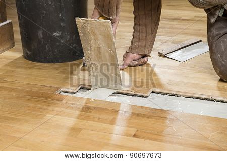 Carpenter Applying Parquet Glue