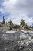 stock photo of hilltop  - Clouds stretch across sky of evergreen tree covered hilltop - JPG
