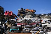pic of wrecking  - Scrap yard for obsolete motor cars with old wrecks and stripped vehicles piled high into the air on top of one another under a sunny blue sky - JPG