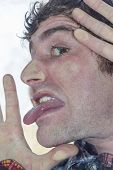 image of lunate  - Crazy lunatic man smooshes face against glass surfaces - JPG