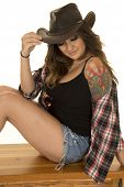picture of cowgirls  - a cowgirl sitting on a bench with her plaid shirt falling off of her shoulder with a tattoo showing - JPG