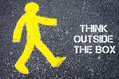 image of thinking outside box  - Yellow pedestrian figure on the road walking towards THINK OUTSIDE THE BOX - JPG