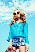 picture of blouse  - Gorgeous young woman with beautiful wavy hair wearing casual blouse and jeans shorts posing outdoor - JPG