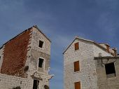 stock photo of opposites  - Two historic houses opposite a blue sky in Kastel Novi at the coast of the Adriatic sea in Croatia - JPG
