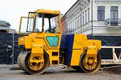 stock photo of heavy equipment operator  - Heavy yellow roller compactor asphalting the town road - JPG