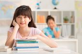 stock photo of schoolgirls  - Asian schoolgirl with a stack of books sitting at her desk - JPG