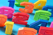 image of blue things  - Colorful plastic numbers close up on a blue background - JPG