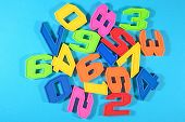 stock photo of blue things  - Colorful plastic numbers on a blue background - JPG