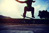 picture of parking lot  - young woman skateboarder doing ollie trick at parking lot - JPG