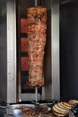 pic of souvlaki  - Pork gyros on vertical broiler rotisserie machine and grilled pita souvlaki bread - JPG