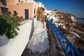 image of runaway  - Runaway bride in a wedding dress in Santorini in Greece - JPG