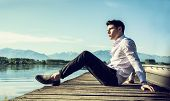 foto of pier a lake  - Handsome young man on a lake in a sunny - JPG