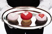 stock photo of cupcakes  - butler holding cupcakes with heart shapes isolated on white - JPG