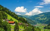 foto of grass area  - Traditional Austrian alipine hous on green grass hill in Zillertal alpine valley against blue sky - JPG