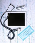 image of medical supplies  - Medical tablet with medical supplies on wooden background - JPG