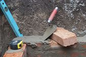 stock photo of trowel  - against the background of the brickwork is trowel level and tape measure - JPG