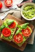 stock photo of cutting board  - Vegan sandwich with avocado and vegetables on cutting board - JPG