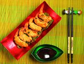 picture of deep  - traditional Vietnam deep fried shrimp and pork rolls in breadcrumbs served on a traditional bamboo place mat - JPG