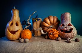 stock photo of carving  - Carved pumpkins old book nuts and witch hat from felt on the branch at Halloween party - JPG