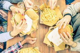 stock photo of burger  - Group of friends toasting beer glasses and eating at fast food - Happy people partying and eating in home garden - Young active adults in a picnic area with burgers and drinks ** Note: Shallow depth of field - JPG
