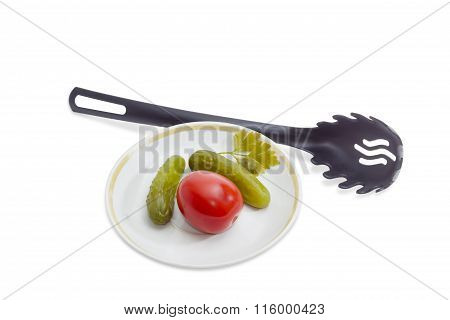 Pickled Cucumbers And Tomato On Saucer And Black Slotted Spoon