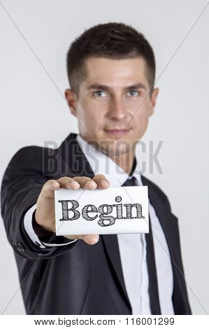 Begin - Young Businessman Holding A White Card With Text