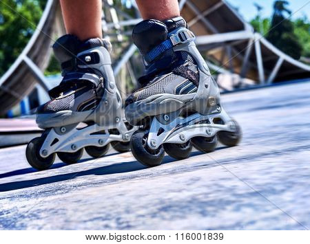 Kids feet wearing roller skate  in skatepark. low section.