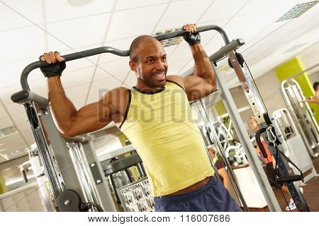Athletic ethnic man training in gym.