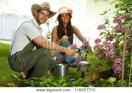 Attractive young couple gardening together at springtime, smiling happy.