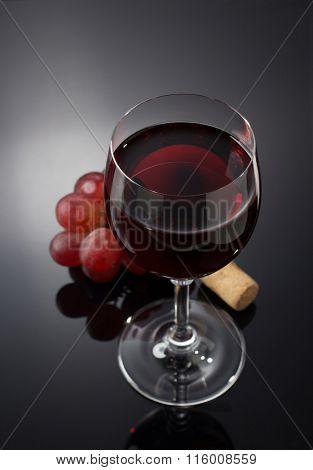 wine glass and grapes on black background