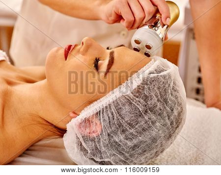 Close up of young woman wearing medical hat receiving electroporation  facial therapy at beauty salon.