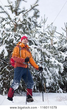 A man walking in the snow with a backpack.