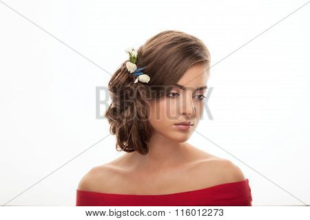 Young cute brunette woman in red blouse with low bun hairstyle and flower headpiece showing trendy m