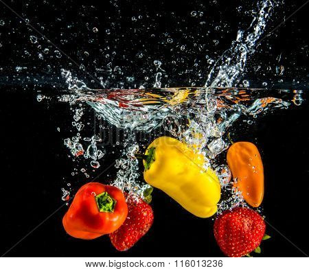 colorful peppers splashing in water