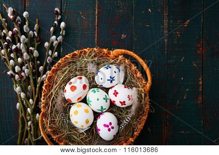 Painted Easter Eggs In Basket And Willow Branches On Wooden Table