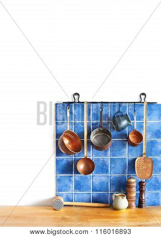 Hanging copper kitchenware set. Spoon, skimmer, grater. Blue tiles ceramic wall. spoon, pitchers, sp
