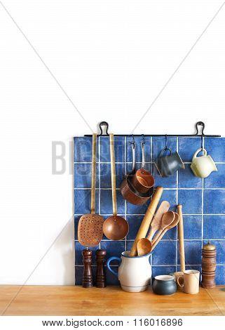 Kitchen brass utensils, chef accessories. Hanging copper kitchenware set. Blue tiles ceramic wall. s