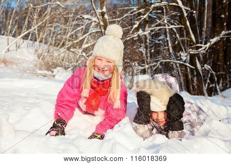 Two little girls wearing winter clothing having fun playing in a fresh snow outdoors