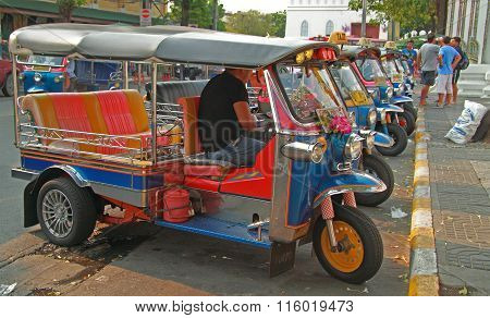 driver of tuk-tuk waits for clients