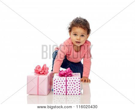 baby girl with birthday presents and confetti