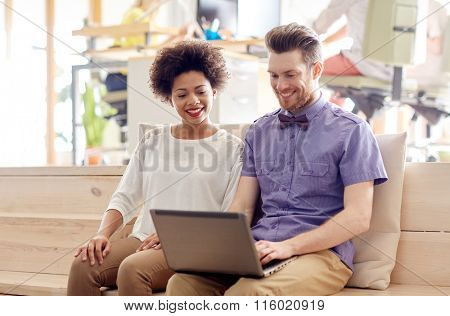 happy creative team with laptop in office