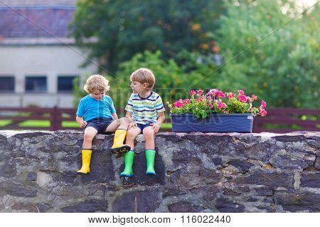 Two little kid boys sitting together on stone bridge
